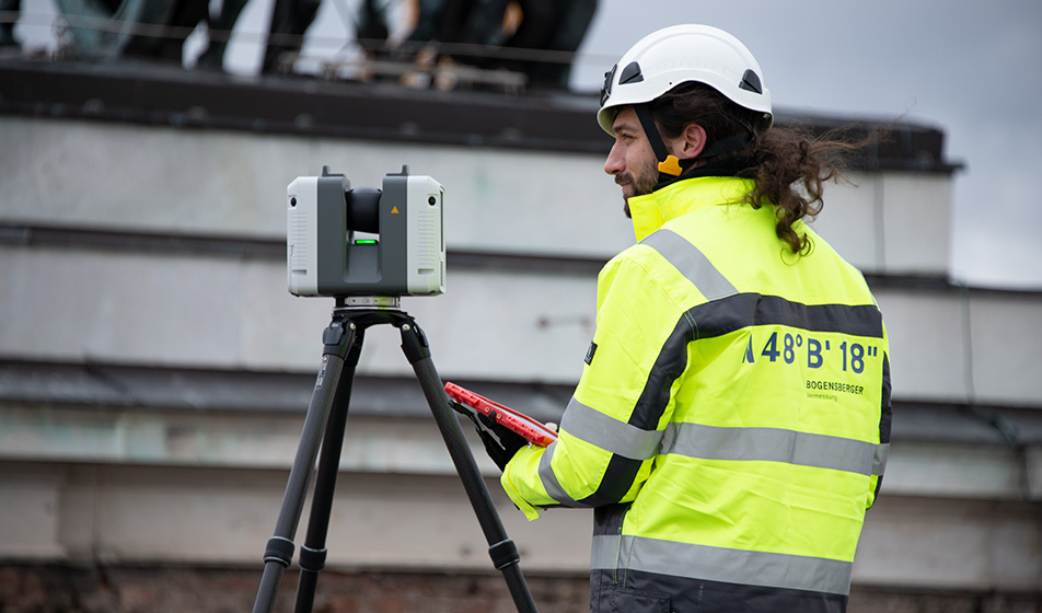 An employee at the building site of the Austrian parliament with a Leica RTC 360 3D laserscanner.
