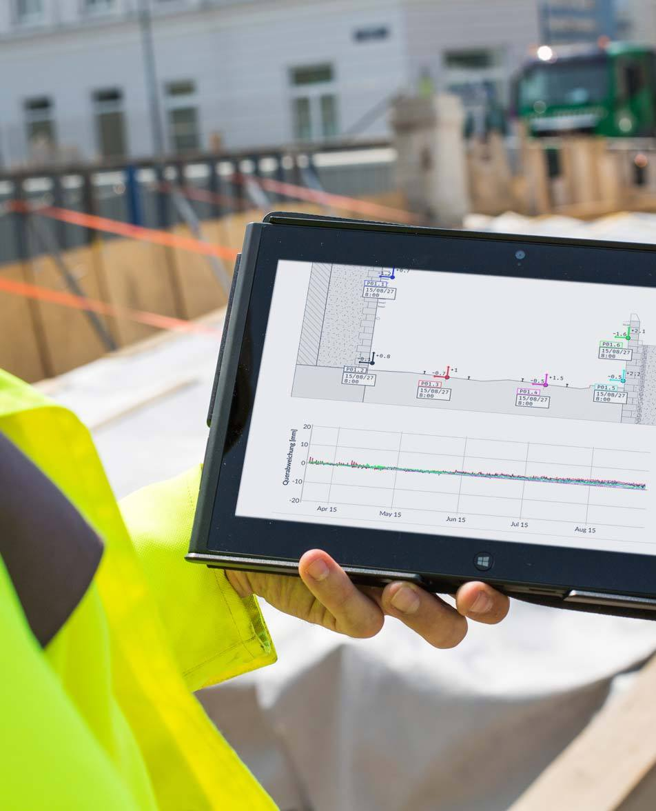 A member of Bogensberger Vermessung / Surveys is holding a tablet which shows the geomonitoring data of the DiMoSy geomonitoring system.